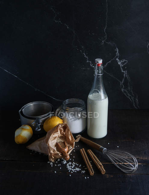 Rustic arrangement of rice, milk, spices and lemons on black wooden table with utensil — Stock Photo