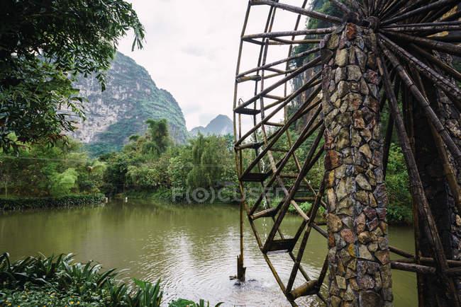 Roue à eau en bois de vieux moulin à eau en pierre dans les arbres sur la rive de la rivière Quy Son avec de magnifiques montagnes sur le fond, Guangxi, Chine — Photo de stock