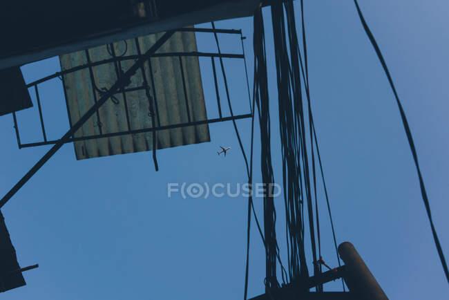 Знизу вибиті кабелі та металевий дах з видом на площину, що летить високо в синьому небі. — стокове фото