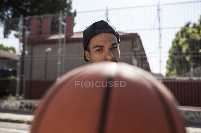 Young afro boy holding basketball on court outdoors — Stock Photo