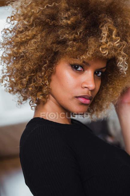 Портрет молодой женщины с кудряшками, чувственно смотрящей в камеру — стоковое фото