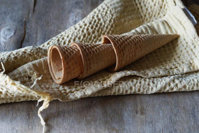 Порожній вафельних ріжків для морозива на полотнище на сірий дерев'яний стіл — стокове фото