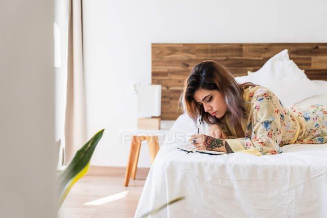 Jovem mulher em roupão de seda deitada na cama e fazendo esboços no bloco de notas no quarto elegante — Fotografia de Stock