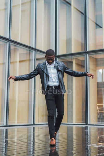 Jeune homme ethnique en vêtements élégants et veste en cuir équilibrant sur le trottoir contre le bâtiment en verre — Photo de stock