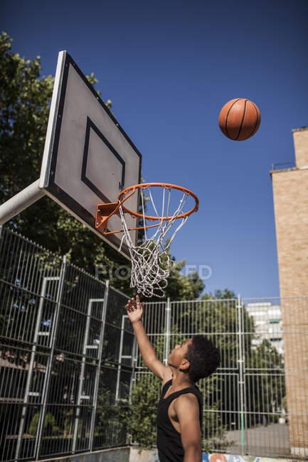 Мальчик-подросток, нацеленный на баскетбол в корзине на открытом воздухе — стоковое фото