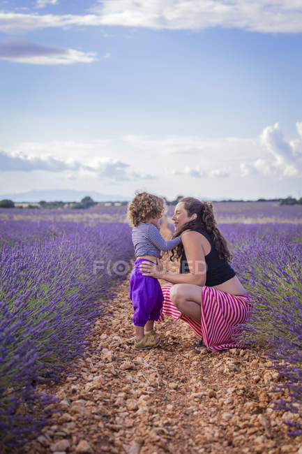 Pregnant woman with child resting in lavender field — Stock Photo