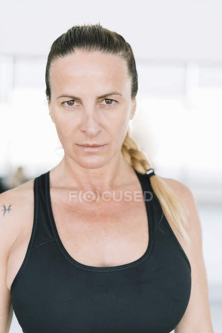 Confident woman in sportswear standing in gym and looking at camera — Stock Photo