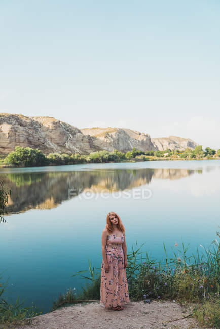 Young woman in long dress standing on rocky shoreline of calm lake with rocky cliffs on background — Stock Photo
