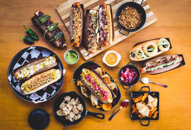 Різні подається хот-доги з різними начинками і закуски на дерев'яні таблиці — стокове фото