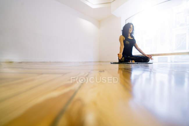 Брюнетка женщина, размышляя на полу в классе — стоковое фото