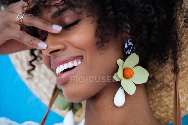 Mulher negra bonita sorrindo usando brincos grandes e um chapéu de palha — Fotografia de Stock