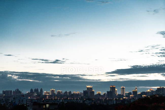 Panorama del horizonte de la ciudad de Sanya desde el parque Phoenix con luces brillantes en el crepúsculo, provincia de Hainan, China - foto de stock