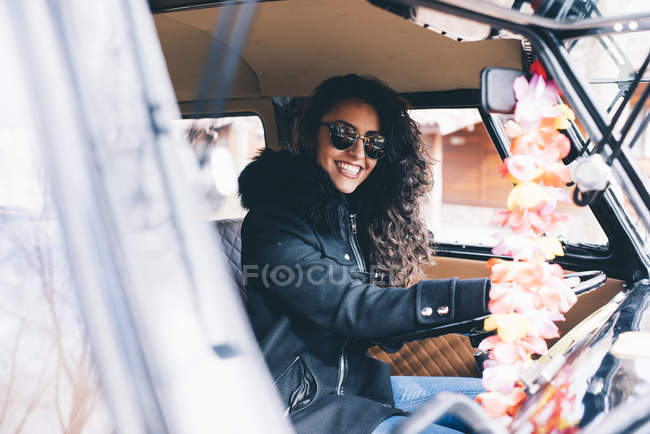 Smiling young woman in black coat and sunglasses sitting inside car — Stock Photo