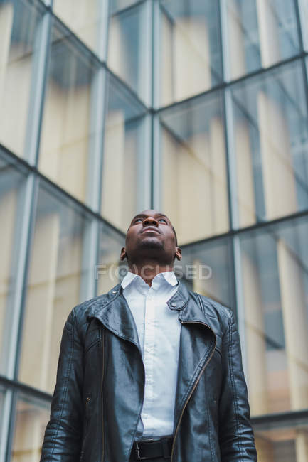 Стильный молодой человек в элегантной одежде и кожаной куртке, смотрящий на современное стеклянное здание — стоковое фото
