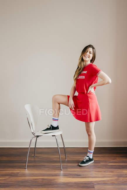 Fille souriante en tenue rouge posant avec une jambe sur la chaise — Photo de stock