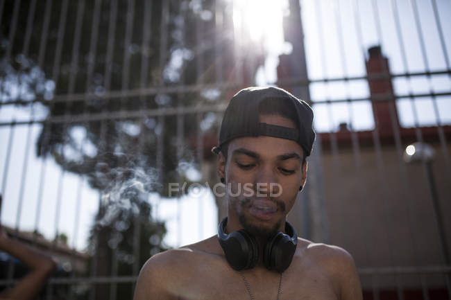 Afro young boy listening to music with headphones while smoking in front of grating — Stock Photo