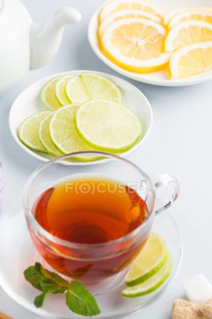 Thé noir en coupe en verre avec la cassonade, de cannelle, de menthe et de tranches d'agrumes sur des soucoupes, théière sur fond blanc — Photo de stock