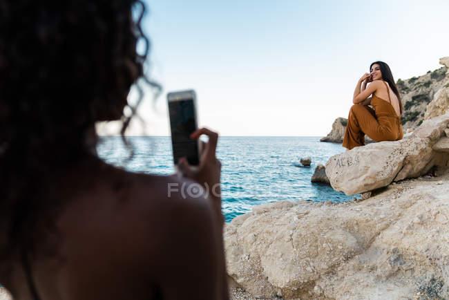 Donna nera che scatta foto con smartphone di un amico elegante seduto sulla scogliera rocciosa del mare in estate — Foto stock