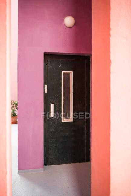 Velho preto elevador de metal em um edifício rosa — Fotografia de Stock