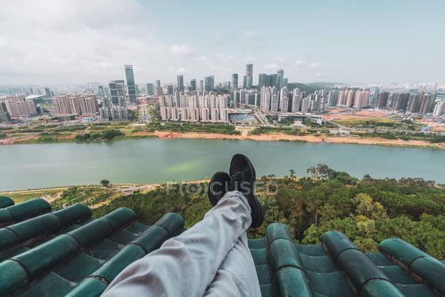 Ноги туристичних на даху з міський пейзаж на фоні, Наньнін, Китай — стокове фото