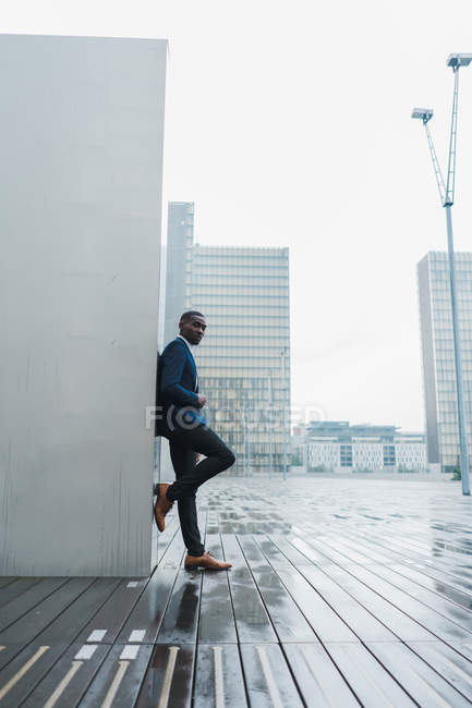 African American businessman leaning on wall outdoors with modern buildings on background — Stock Photo
