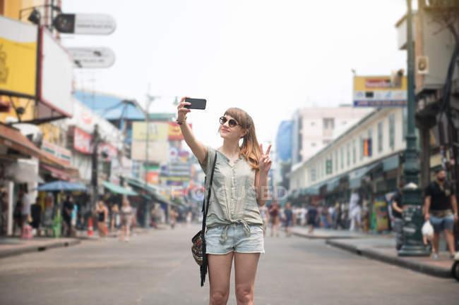 Femme gaie prenant selfie et geste deux doigts dans la rue en Thaïlande — Photo de stock