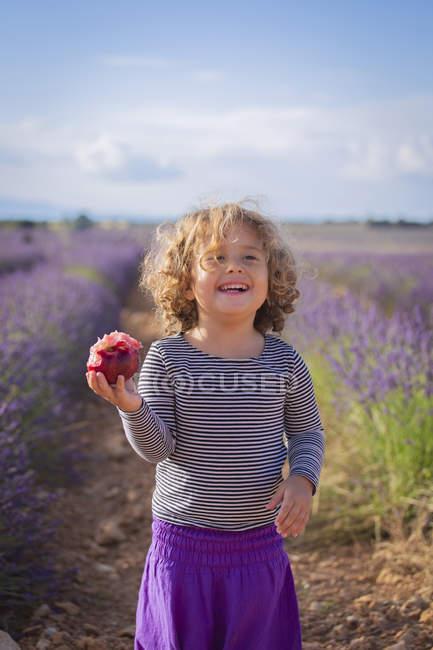 Смеющаяся маленькая девочка с персиком, стоящая на лавандовом поле — стоковое фото