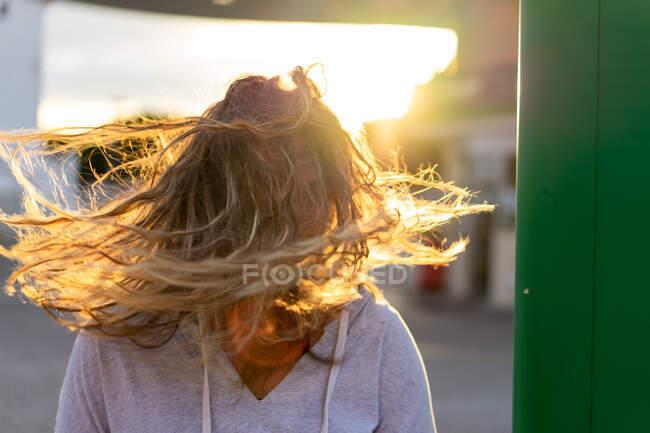 Fröhliche junge Frau mit leicht bewegtem Haar bei Sonnenuntergang — Stockfoto