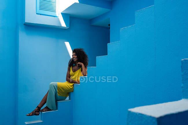 Чорна жінка сидить на сходах синього будинку.. — стокове фото