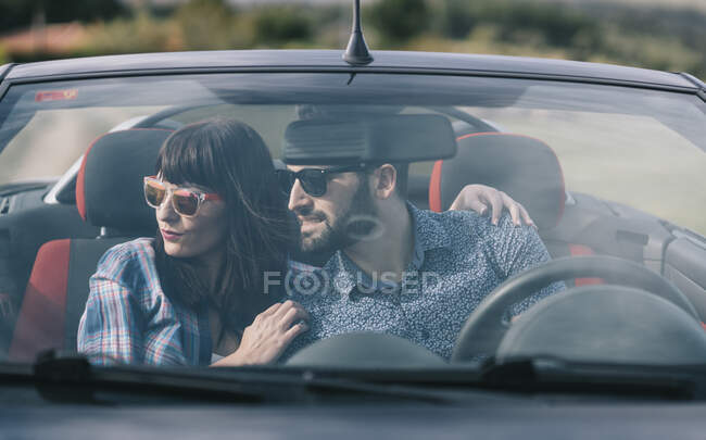 Brunette woman in casual clothes and bearded man in shirt sitting in dark car and looking away — Stock Photo