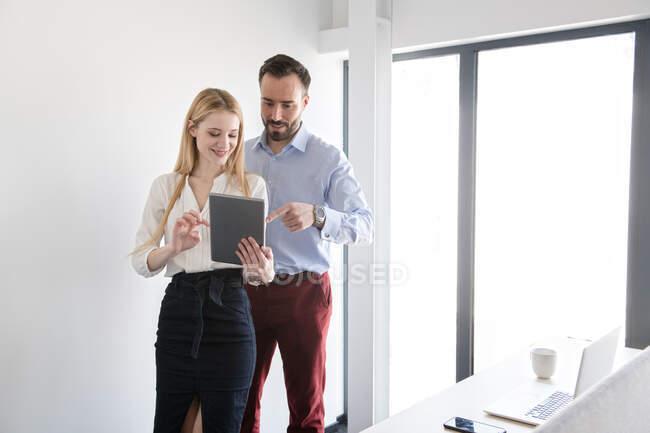 Elegante sonriente hombre y mujer de pie en la oficina de luz y el uso de la tableta juntos durante la discusión - foto de stock