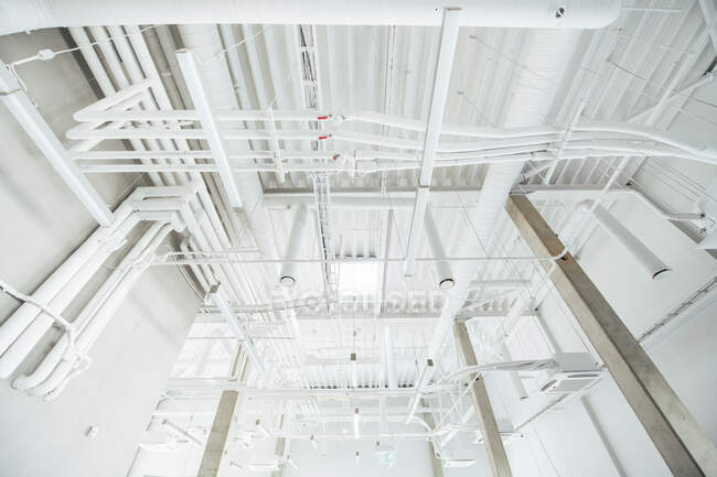 From below shot of spacious building interior with white pipes and air systems hanging in daylight — Stock Photo