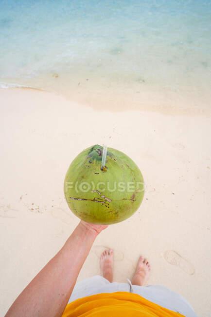 Crop man holding green coconut on beach — Stock Photo