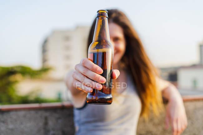 Счастливая женщина показывает коричневую бутылку пива на крыше — стоковое фото