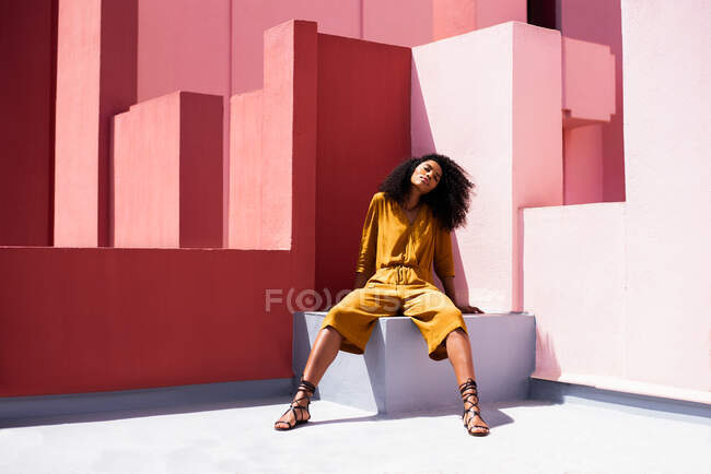 Black woman sitting in a colorful wall — Stock Photo