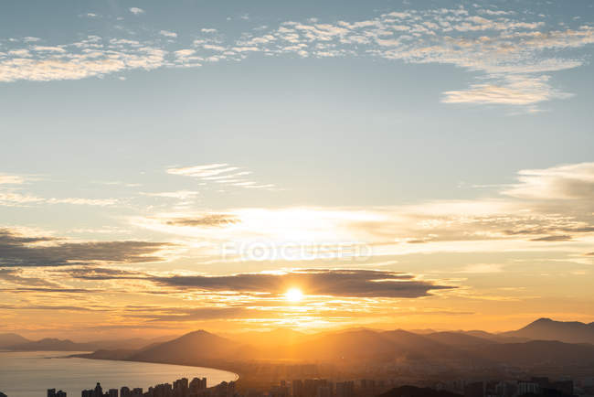 Bright sunset over mountains and coastal cityscape, Sanya, Hainan Province, China — Photo de stock