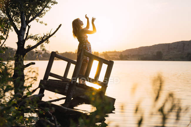 Woman standing on sunken pier at lake in sunlight — Stock Photo