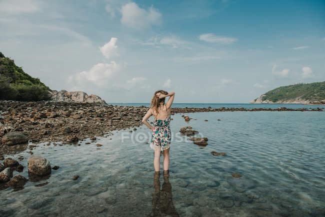 Жінка в літні плаття стоїть на скелястий берег на морі в Таїланді — стокове фото