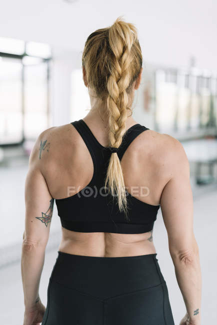 Back view of female athlete in black sportswear standing in gym — Stock Photo