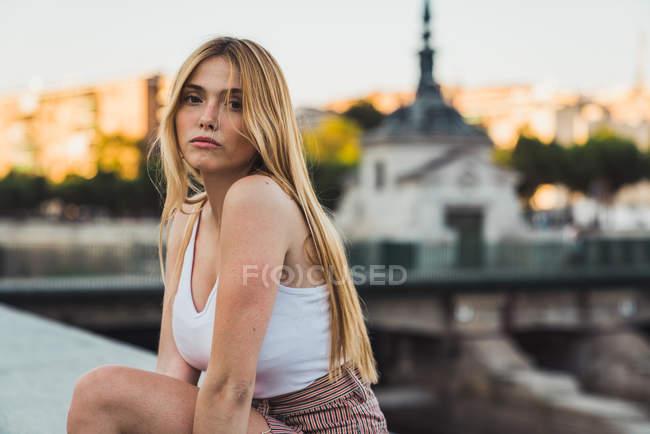 Jovem loira em roupa casual olhando para a câmera enquanto sentado na cidade — Fotografia de Stock