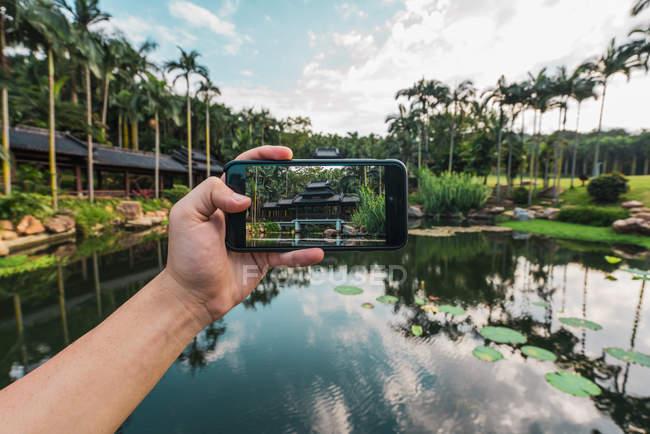 Рукою людини фотографують з смартфон Східні забудови на тропічний озеро гора Qingxiu, Китай — стокове фото