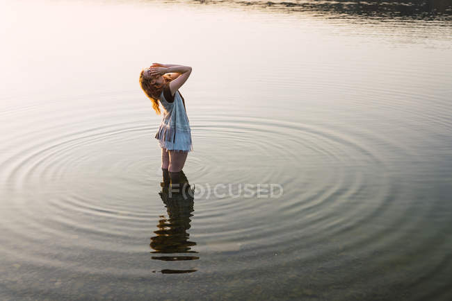 Жінка, стоячи в прозорій воді озера і зворушливо волосся — стокове фото