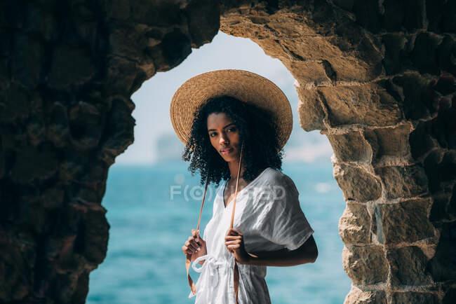 Черная женщина в соломенной шляпе на древних руинах у моря — стоковое фото