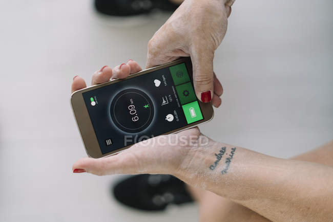 Hands of female athlete using fitness app on smartphone — Stock Photo
