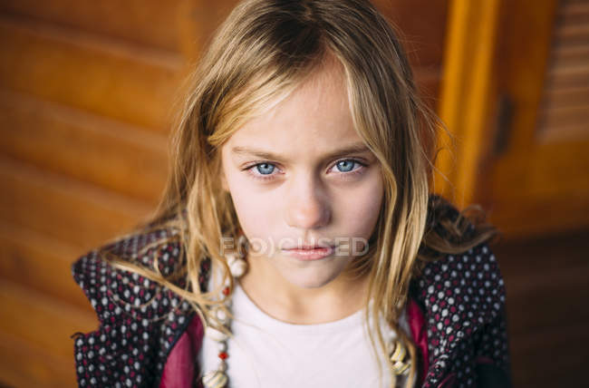 Portrait of blond girl with blue eyes standing wooden background — Stock Photo