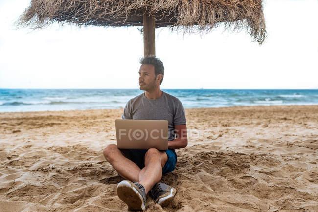 Людина, що спирається на солом'яну парасольку на пляжі працює на комп'ютері — стокове фото
