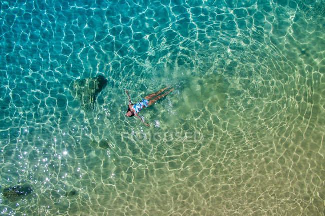 Vista aérea da mulher em roupa de banho brilhante deitada na superfície da água azul-turquesa — Fotografia de Stock
