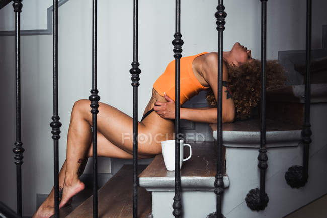 Alluring ethnic woman in top and panties lying sexually on steps with coffee cup — Stock Photo