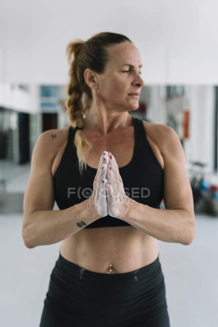 Блондинка разбрасывает мел на руки во время тренировки в спортзале — стоковое фото