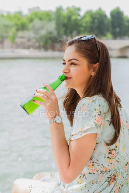 Молодая женщина в летнем платье пьет воду на набережной — стоковое фото